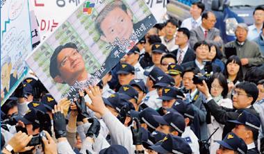 2008 年三星前總裁李健熙(圖中海報右者)涉嫌逃稅、行賄下台,民眾上街抗議財閥惡勢力橫著走(圖中海報左者為三星現任總裁李在鎔)。