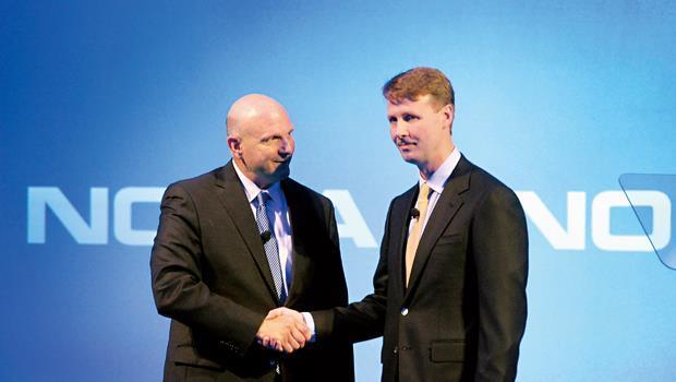 微軟執行長鮑默(左)與諾基亞董事長席拉斯瑪(右)攜手,前者以低於市場行情的約新台幣2億元收購後者。然而,這場划算交易,不一定會為兩者加分。