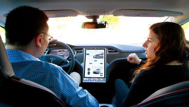 商周採訪團隊在特斯拉員工(右)陪同下,親身試駕電動車,外觀看來無異於一般房車,但整個車內空間與結構設計,卻完全顛覆百年汽車工業。