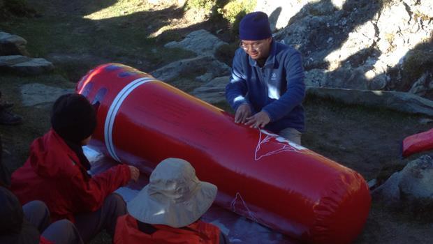 王士豪醫師在嘉明湖避難山屋,示範如何使用攜帶型加壓袋。(王士豪醫師提供)圖中紅色的攜帶型加壓袋(PAC),充氣後,可讓加壓袋內的壓力,達到下降海拔1500到1800公尺的效果,有機會拯救因低壓缺氧而嚴重高山症的患者,免於死亡。