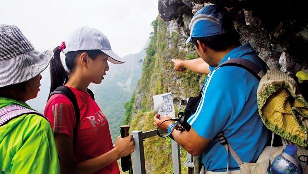 錐麓古道嚮導 楊偉仁,善用照片比對的方式解說錐麓古道。他手指前方山岳的「打勾」痕跡,根據老照片,日據時代就已留下此痕跡。