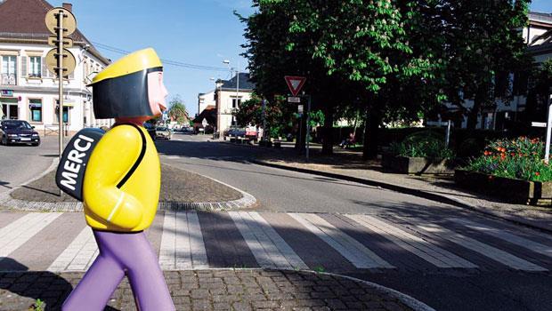 斑馬線旁,立了個背著書包的兒童雕像,似乎也正等著過馬路,書包上還用法文寫著「MERCI(謝謝)」