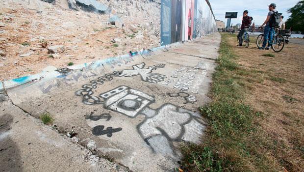柏林圍牆旁的塗鴉,控訴臉書、金錢洗腦,讓和平成為犧牲品。當政府的手伸進臉書,結果會是什麼?