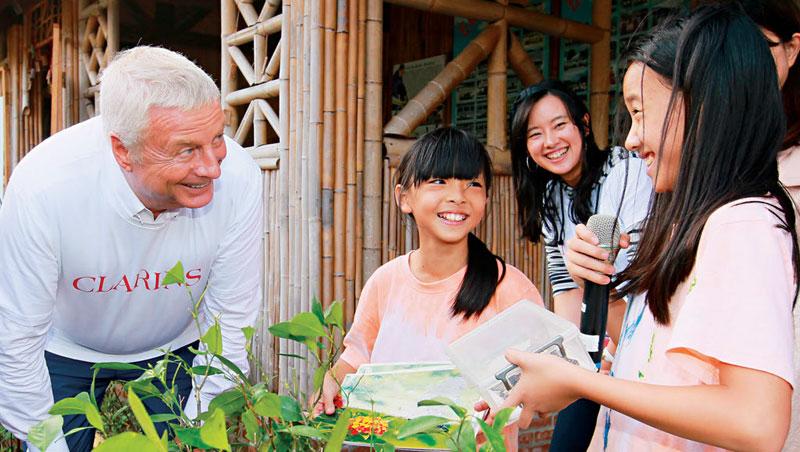 蘭詩集團主席克利斯汀‧古登—克蘭詩,仔細聆聽五寮國小的小解說員解說校園生態。
