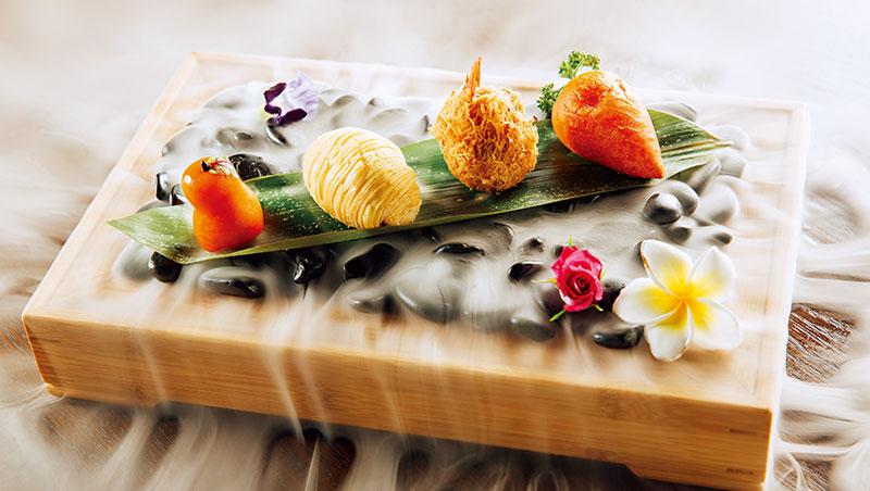 在炎香樓用餐好比欣賞一場表演,將茶具鋪上黑色鵝卵石,粽葉擺著西洋梨芋香愛窩窩(左起)、蘿絲酥、芋角、人蔘果,上桌時以乾冰呈現,作風新派。