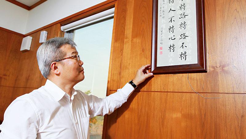 巧新前總經理石呈澤(圖),手指著的書法字正像他此刻的心境,身為戰將,卻在2 個月內生涯劇烈轉彎。