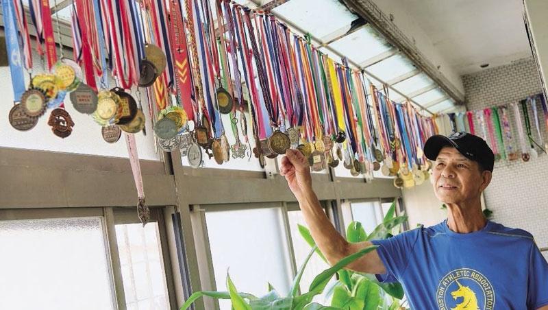 成排獎牌高掛家裡陽台,輕輕撥動,像風鈴一樣叮鈴作響。