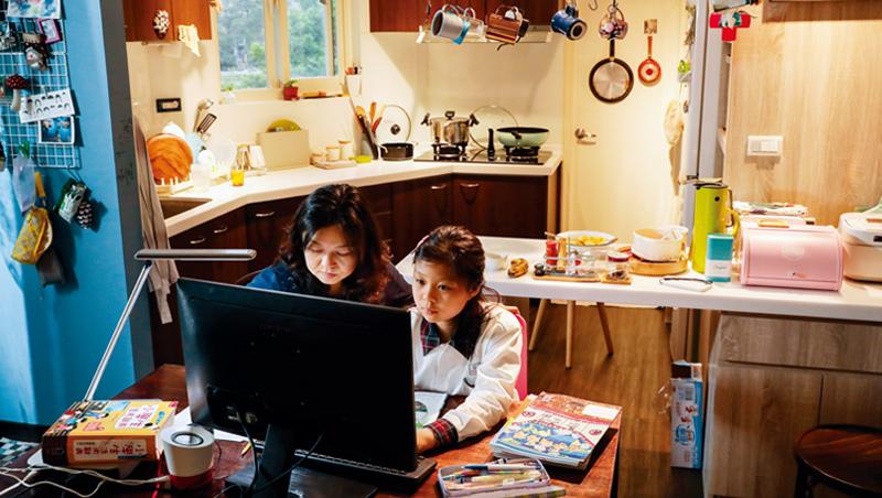 放學後,國小三年級的孩子在家人陪伴下在家遠距線上學習,而她的「上課區」,就在母親料理三餐的廚房前。