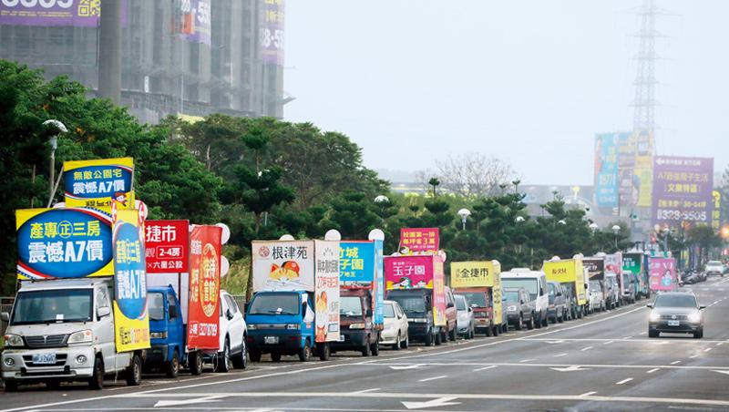 房市太熱了!桃園機場捷運A7站的大馬路,排了10幾輛,掛著建案廣告的卡車,目標是台北來的買房客。
