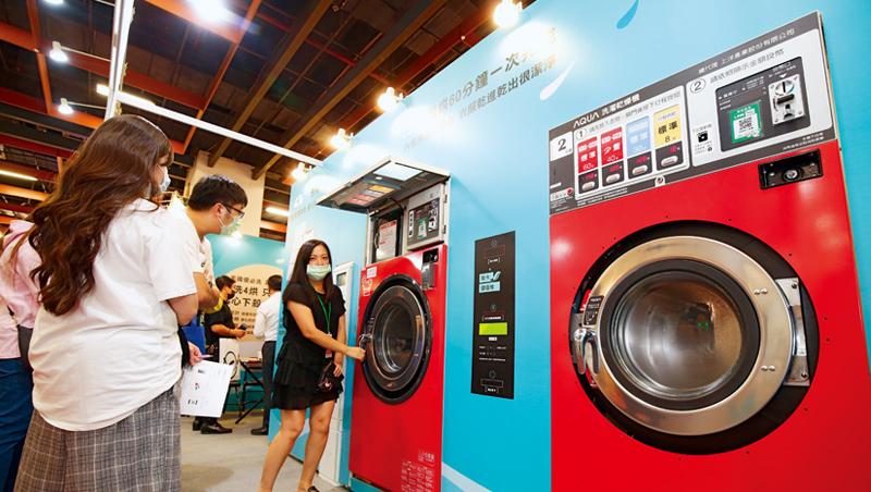 10月台北國際加盟展中,自助洗衣店加盟總部員工,正向加盟主說明洗脫烘三合一的洗衣設備優勢。
