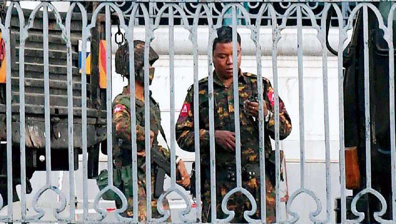 緬甸軍方在仰光市政廳看守。政變為緬甸因疫情受挫的經濟狀況再雪上加霜。