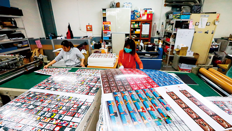廠內正趕印一副副花牌,整片印刷後再裁切、品檢、裝盒,即可出貨。