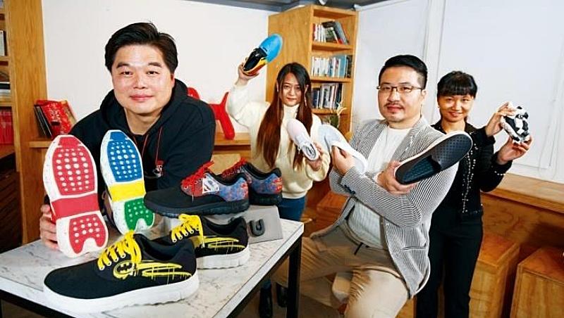 歷經品牌重生,許佳鳴(左1)將環保鞋訂為公司主軸,如桌上一紅、一藍2雙鞋底,正是以該顏色的飲料寶特瓶製作而成。