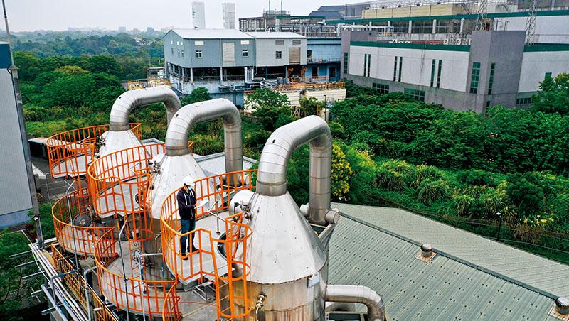 圖中工作人員所在地,是友達為擺放零排放設備,在廠外找到的一片800多坪畸零地;而圖後方的廠房,就是友達龍潭廠