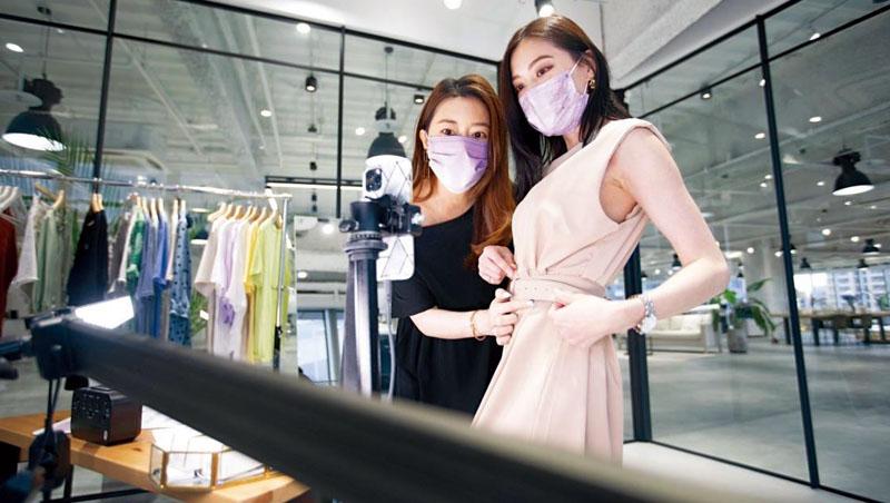 周品均(圖左)在公司直播細心為網友講解衣服的材質、適合身形