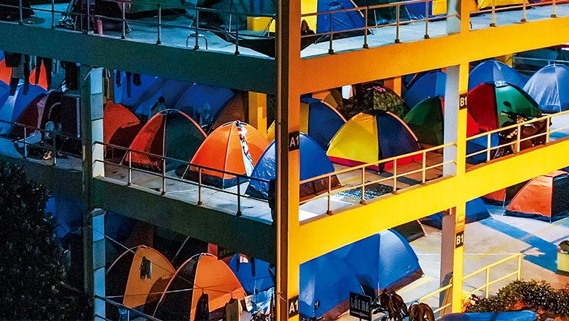 廠區空地架起一座座五顏六色的帳篷,供員工夜晚休息,成疫情中的特殊風景。圖為日本電產越南廠停車場,將男、女工分隔在不同樓層