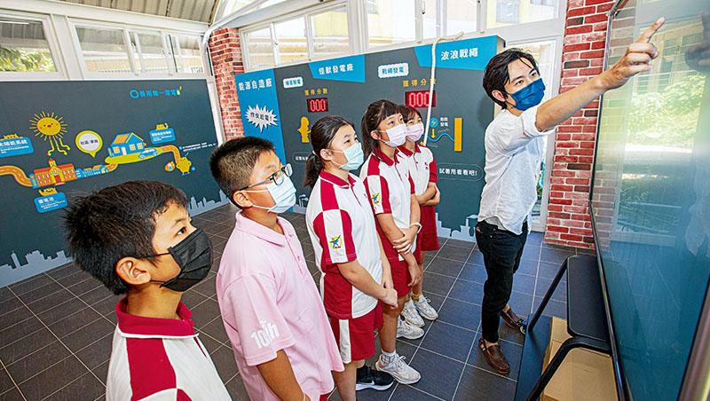 在文欣國小內,學生正在看自己校園的用電及太陽能發電狀況,學校的學務處是校園用電大戶