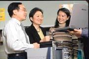 在台灣IBM科技事業群實驗室中,孫中平(中)與同事討論各家大廠筆記型電腦的測試結果。