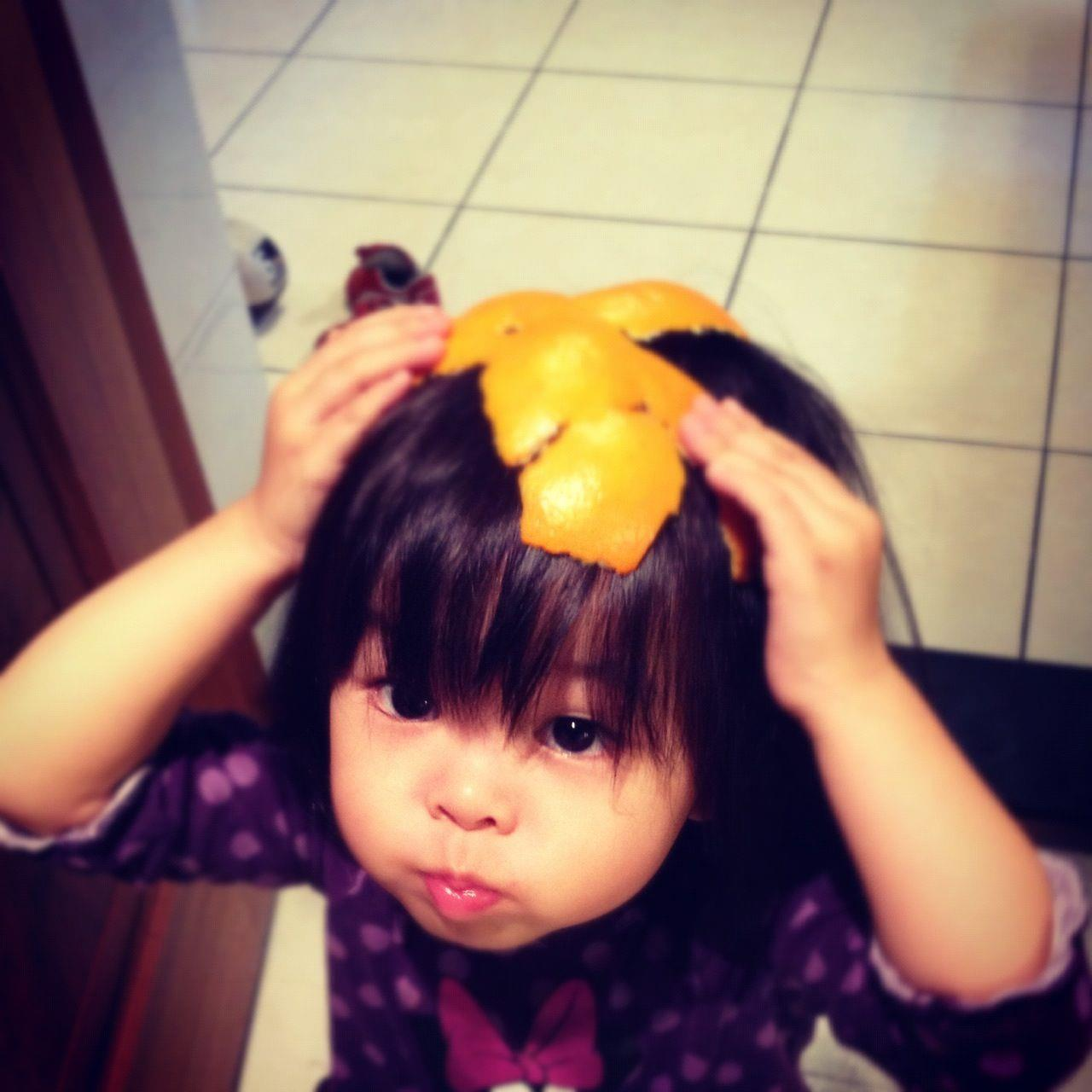 女兒拿著她做的橘子帽給我看