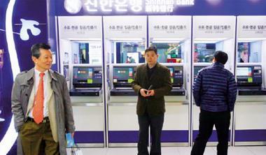 遭駭客重創的南韓企業,須一週才能完全恢復作業,圖為南韓警方與官員在出事的新韓銀行了解狀況。