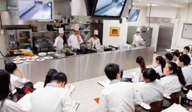 高餐大西廚系在每堂實習課前,必定先在一般教室(圖)示範、解說原理,讓學生了解備足烹飪知識後,才踏進貼近真實戰場、刻意不裝冷氣的廚房實作。