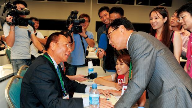 會議空檔,鴻海董事長郭台銘(圖左)貼心幫實習記者簽名,惹來富邦金控董事長蔡明忠(圖右)一陣調侃。