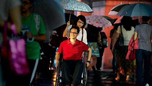 下班時間,許超彥(中)自己推著輪椅、黃述忱(中後)替他撐著傘,他正準備去取車,開車載太太回家,儘管經過磨難,他們的愛還是像物體恆存般,一直都在。