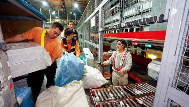 在桃機長榮倉儲,人員忙著分裝國際快遞包裹,其中不乏大陸來的淘寶網購商品,在此透過陸運,向南北輻射出去。