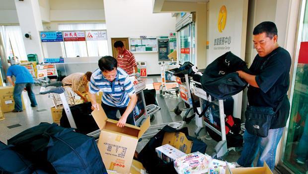 在金門水頭碼頭,「小蜜蜂」忙著拆箱,把台灣來的餅乾、尿布,裝進特製大行李袋,一人扛3、4袋,一團5、6個人上船,運到廈門。