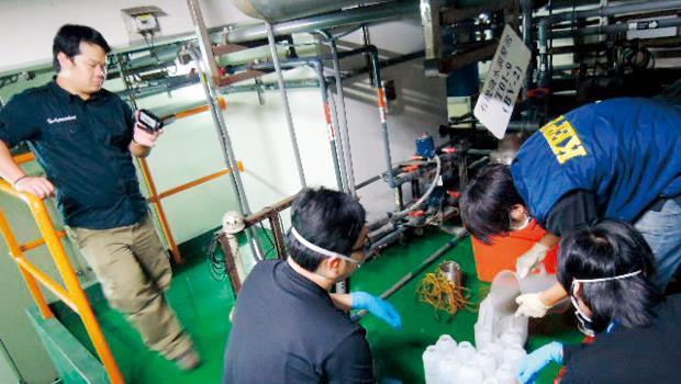 稽查員深入K7廠廢水處理區做120小時馬拉松式蒐證;日月光員工(左1)也諜對諜,忙著在一旁以錄影、拍照方式做反蒐證。