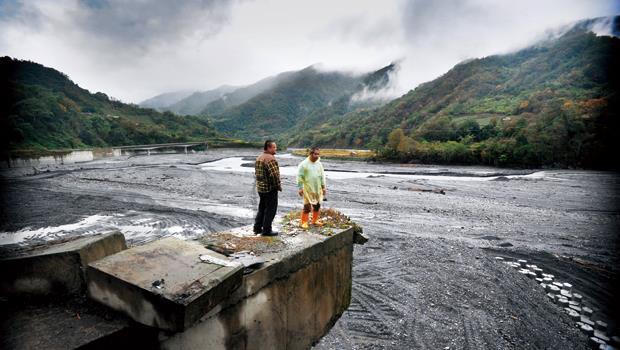 親愛村村長洪文全(左)與村民站在河邊,看著因淤積而面目全非的溪流。