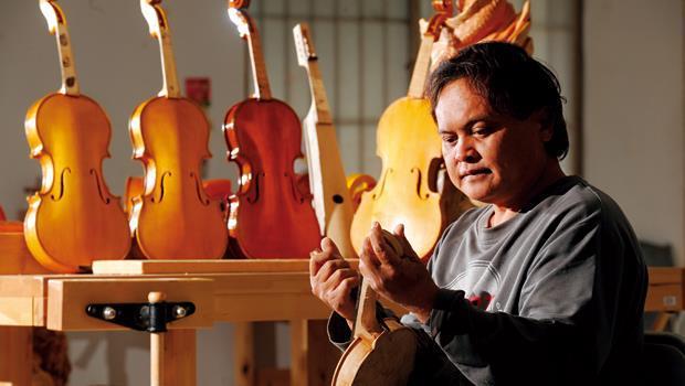 曾到三義學雕刻的林健興(圖)是弦樂工坊的種籽老師,也有孩子正在學小提琴的媽媽,加入製琴行列,他們希望有天親愛村的琴能賣好價錢,未來生活就會不一樣。