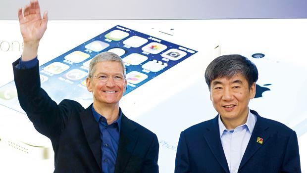 蘋果執行長庫克(左)將在今年推出大計畫,iPhone 6強攻硬體規格,不只反撲三星,更為進軍中國做準備。圖右為中國移動董事長奚國華。