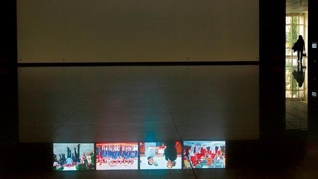 苗栗縣府大樓,牆上螢幕輪播著縣長的政績照。