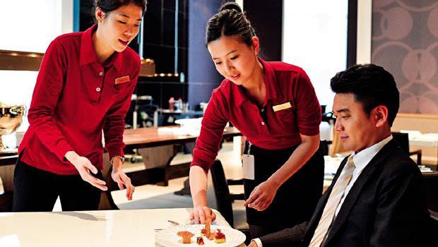 從客人的右邊上菜、置放盤子時不能發出噪音、服務員(中)需面帶微笑,這些細節,在「角色扮演」的訓練中,都需反覆操作,主管(左)會在一旁指導。場景為台北文華東方COCO法式餐廳。