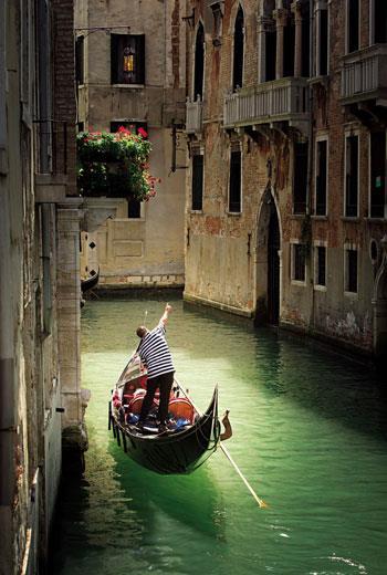 船伕在靠近威尼斯中部的馬寧廣場(Campo-Manin)旁的運河上划著船。