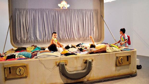 北美館以「禮物」為活動的主題,讓大人跟小孩躺在大行李箱內觀看關於「生老病死」的影片。