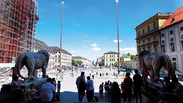 重建,安靜進行中》從希特勒曾登高演說的元帥迴廊看出去,廣場上從過去的追隨者,變成大批度假中的民眾,左側,鐵阿提納教堂主體雖在戰後10年就重建好,至今仍不時圍起鷹架,慢慢修補。