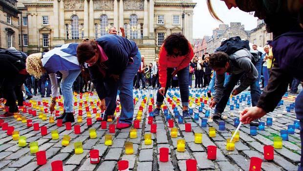 最嚴重的分裂危機,最溫和的解決之道》公投當天,在愛丁堡國會廣場前,西班牙加泰隆尼亞自治區民眾用蠟燭在地上排出象徵獨立的旗幟。