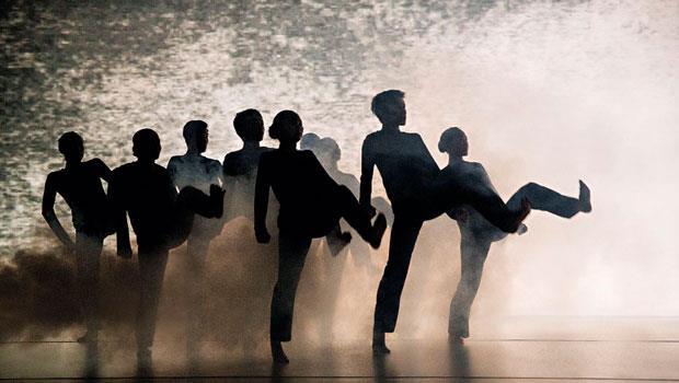 舞台上煙霧瀰漫,舞者掙扎反抗、驚惶奔逃,卻仍被黑影吞噬。