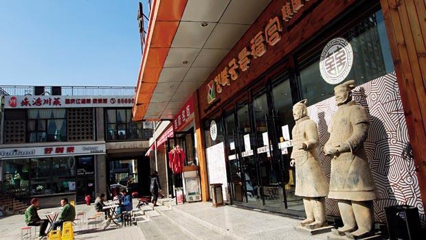 這家以韓國皇宮「景福宮」為名的餐廳門口,居然有中國兵馬俑站崗,看似突兀的組合,成了西安韓國村的獨特景象。