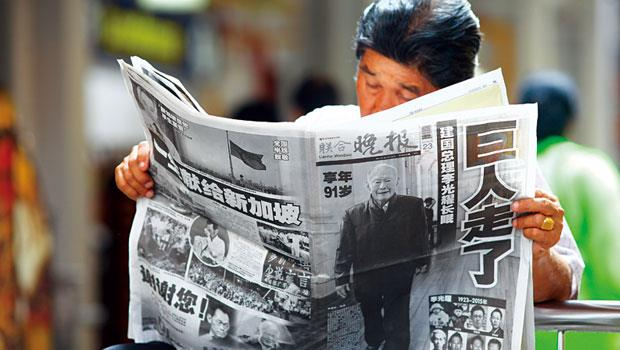 3月23日 16:14 唐人街。巨人走了,打開滿版的黑白報紙,一個華人沉默回顧著李光耀的一生。
