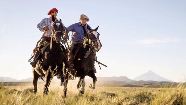 亞拉堤亞(左)與高喬牛仔夥伴克勞迪歐.伊納爾(Claudio Inal)穿過巴塔哥尼亞高原,後方是拉寧火山錐。