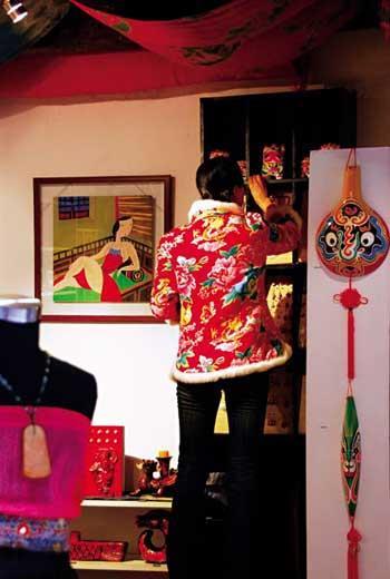 一位穿著紅襖的大姑娘,正站在板凳上擦拭貨架