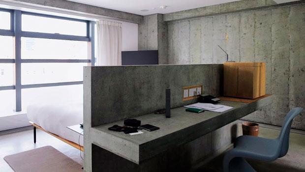 房間內辦公桌採用與牆面相同的水泥材質一體成型,並做出開放隔間,非常具有巧思。