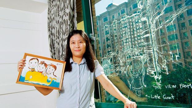 林愛晨手中的畫,是街頭畫家畫的兩個寶貝女兒;窗上的塗鴉,是女兒展露的幸福心聲。