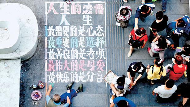 武漢的一位先生用粉筆在地上寫一些人生感悟