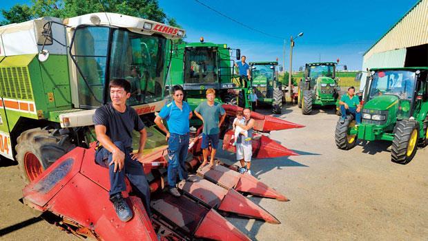 農機是農二代的生財工具,阿麒(著黑衣)腳下那輛紅色火箭頭採收機來自波蘭,全新要價新台幣千萬元以上,透過國際農機拍賣網站,只要三分之一價錢就能入手。