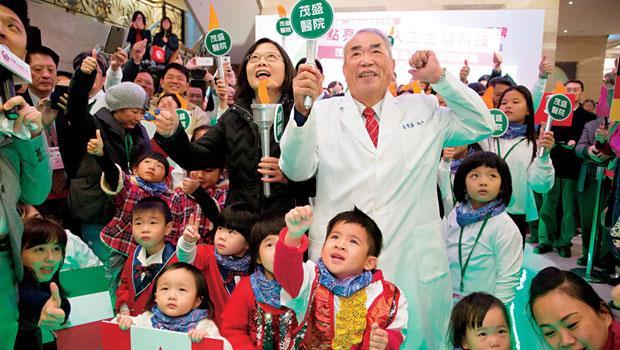 茂盛醫院開幕,蔡英文(圖中左)趕來站台,她感謝院長李茂盛(圖中右)用人脈助綠營再起,與現場的試管寶寶們一起「點亮」台灣人工生殖科技。