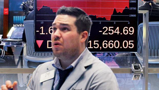 2 月11 日美股被聯準會主席葉倫(左上)鬆口將考慮負利率的消息嚇得重跌,交易員眉頭深鎖思考應對方案。